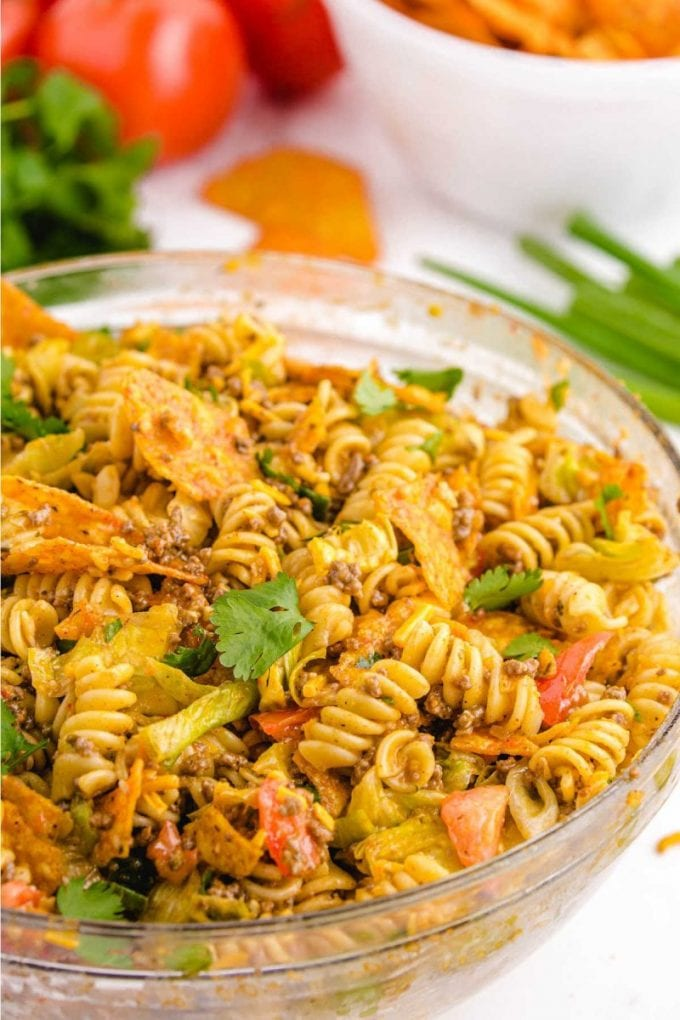 close up shot of taco pasta salad garnished with cilantro in a clear bowl