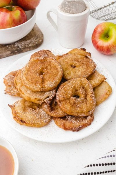 apple fritter rings piled on top of each other and drizzled with powder sugar on a white plate