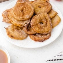 close up shot of apple fritter rings piled on top of each other and drizzled with powder sugar on a white plate