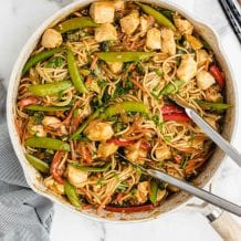 close up overhead shot of chicken lo mein in a pan with tonsils