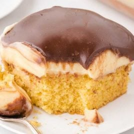 close up shot of a slice of Boston Cream Poke Cake topped with vanilla pudding and chocolate on a plate with a fork