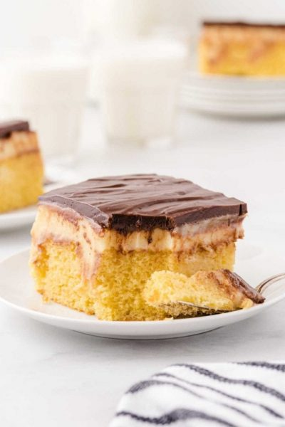 boston cream poke cake with a piece taken out of it on a fork