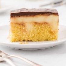 close up side shot of boston cream poke cake on a white plate