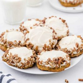 carrot cake cookies with cream cheese frosting piled on a white plate with glasses of milk in the back