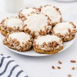 carrot cake cookies with cream cheese frosting piled on a white plate