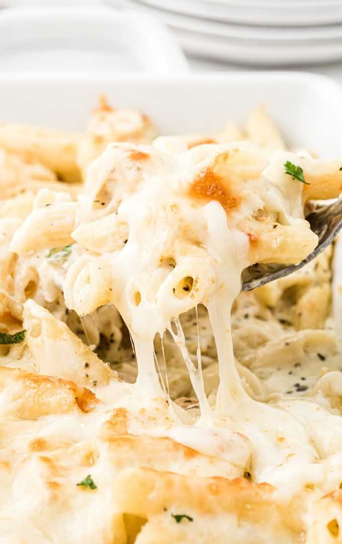 close up shot of creamy chicken alfredo bake being picked with silverware in a baking dish
