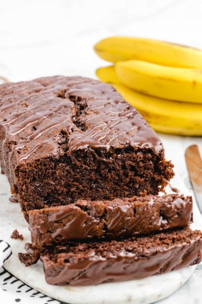 chocolate banana bread with chocolate glaze sliced on a tray with bananas in the background
