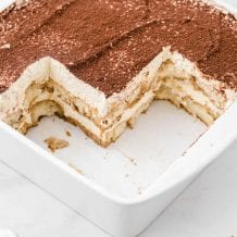 close up shot of easy tiramisu recipe in a baking dish with slices missing