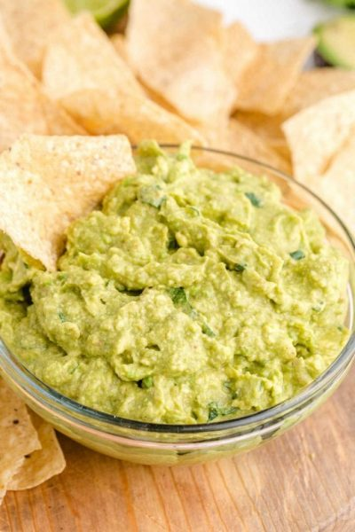 a bowl of guacamole with chips on a wooden board