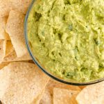 close up overhead shot of guacamole in a clear bowl with chips
