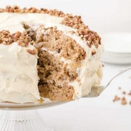 side shot of hummingbird cake with pecans on top with a slice being taken out of it on a cake dish