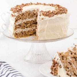 side shot of hummingbird cake with pecans on top with a slice missing on a cake dish