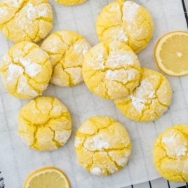 overhead shot of lemon crinkle cookies with lemon slices on a cookie sheet that is placed on a rack