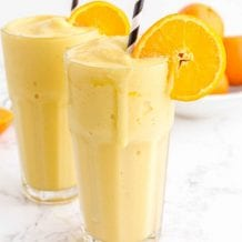 close up side shot of orange julius in glasses with a stripped straw garnished with a slice of orange
