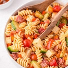 close up shot of pasta salad in a bowl with wooden spoons