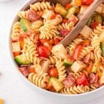 close up shot of pasta salad in a bowl with a wooden spoon