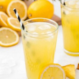 a glass of pineapple lemonade with ice and lemon slices