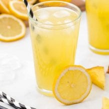 close up shot of a glass of pineapple lemonade with ice and lemon and pineapple slices