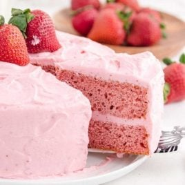 side shot of strawberry cake with a slice being taken out of it with a spatula