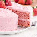 close up side shot of strawberry cake with a slice being taken out of it with a spatula