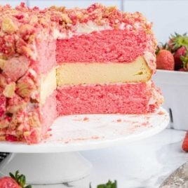 side shot of strawberry shortcake cheesecake with a slice missing showing its inside layers on a cake rack