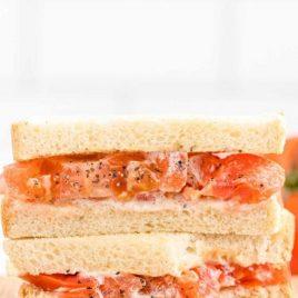 side shot of tomato sandwich on a wooden board