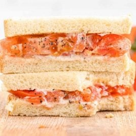 close up side shot of tomato sandwich on a wooden board