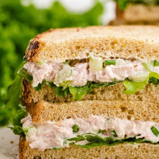 close up side shot of the layers of tuna sandwich stacked on top of each other