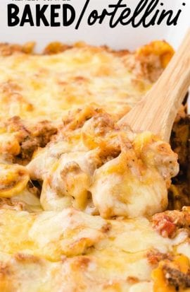 close up shot of baked tortellini topped with melted cheese in a baking dish being picked up with a wooden spoon