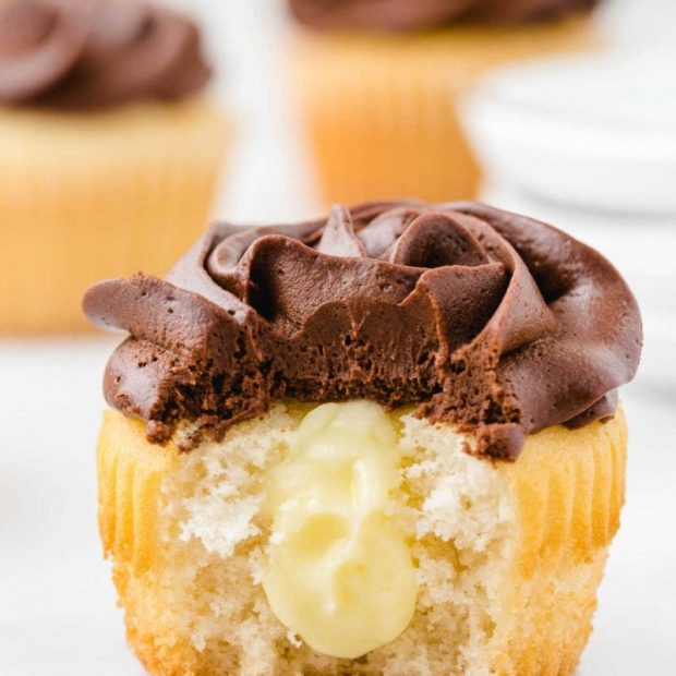 boston cream cupcakes with chocolate frosting with a bite taken out of it showing its cream cheese filling inside