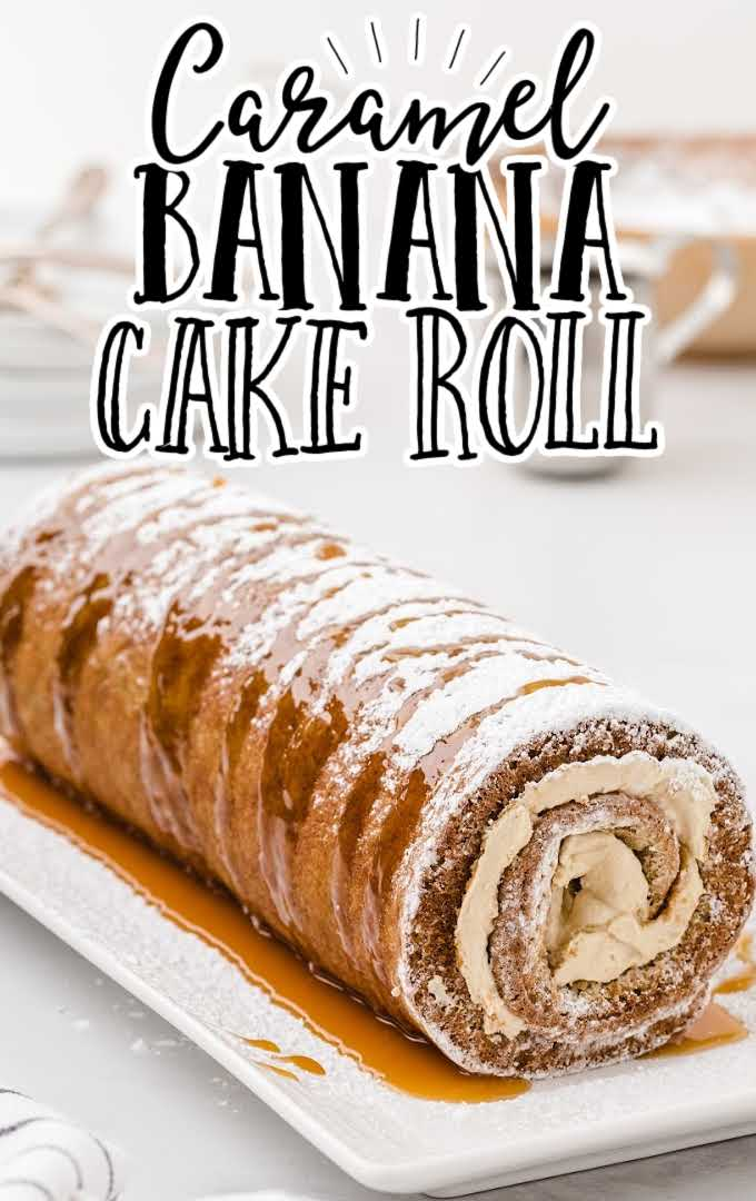 caramel banana cake roll drizzled with caramel sauce and dusted with powdered sugar on a plate