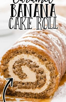close up shot of caramel banana cake roll drizzled with caramel sauce and dusted with powdered sugar on a plate
