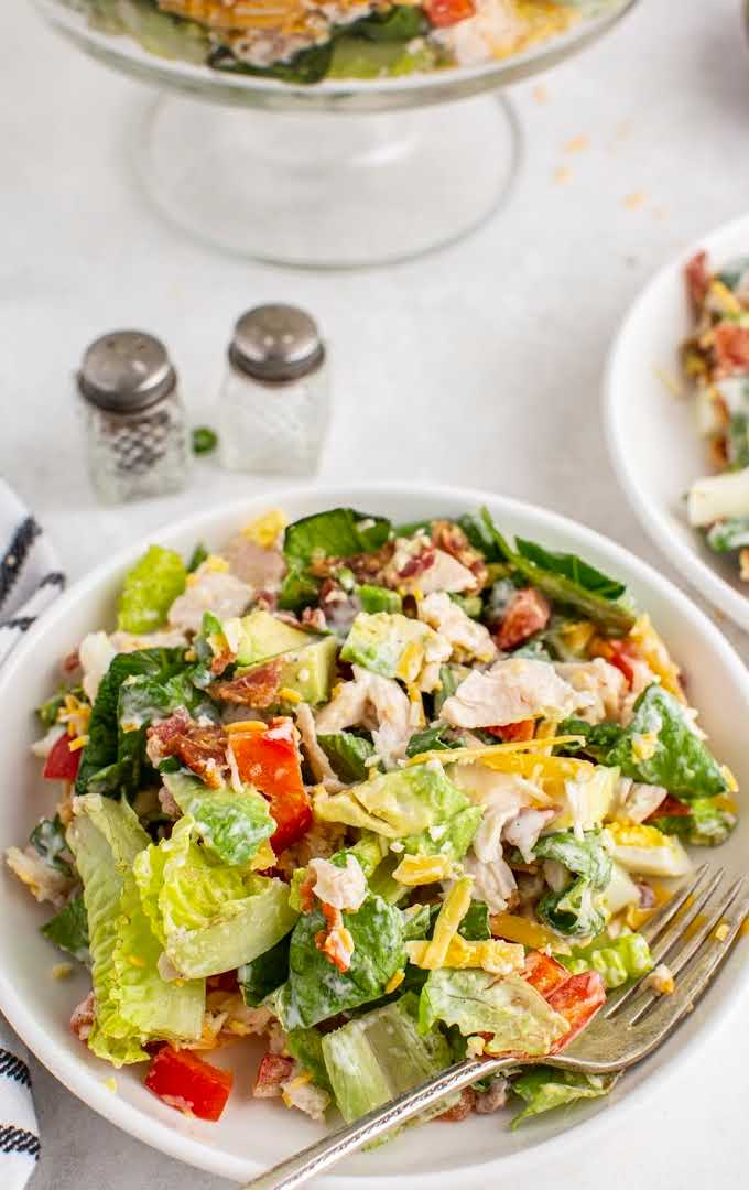 chicken bacon ranch salad with ranch dressing on a plate with a fork