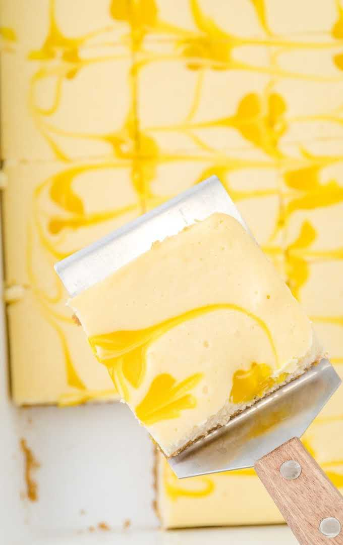 overhead shot of lemon cheesecake bars in a pan with a slice being picked up with a spatula