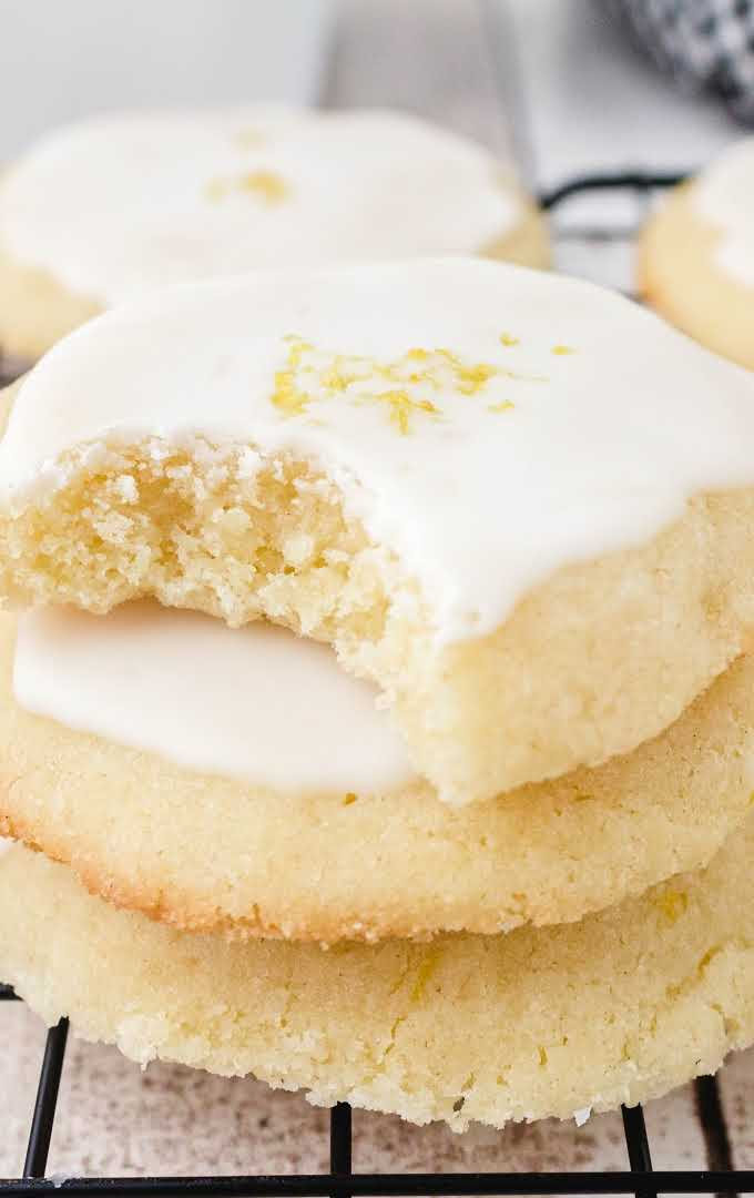 close up shot of lemon meltaway cookies stacked on top of each other on a rack with a bite taken out of one