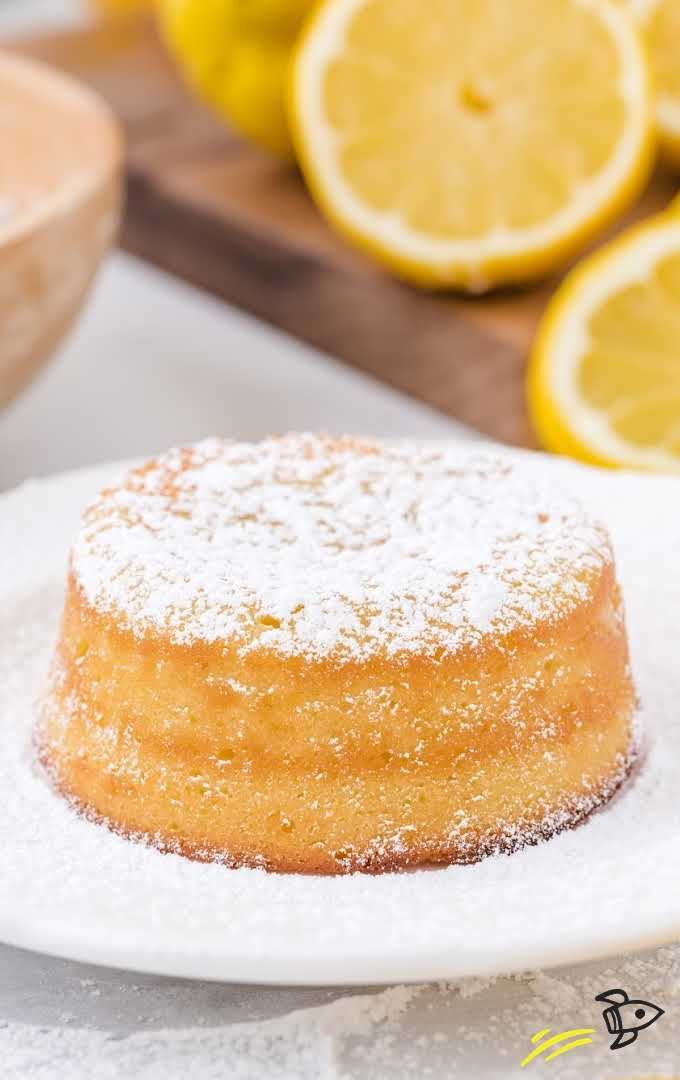close up shot of lemon lava cake dusted with powdered sugar on a white plate