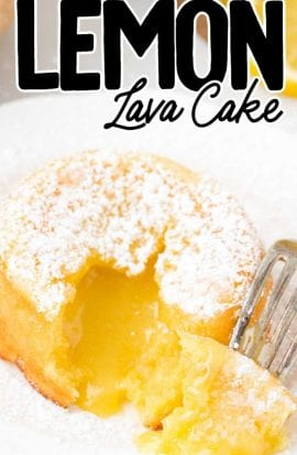 close up shot of lemon lava cake dusted with powdered sugar with a bite taken out showing its inside lemon layers on a white plate