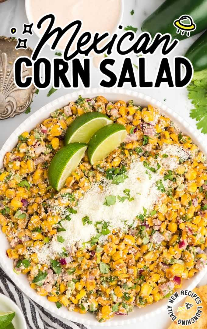 close up overhead shot of Mexican corn salad garnished with parsley then topped with Cotija cheese and lime slices