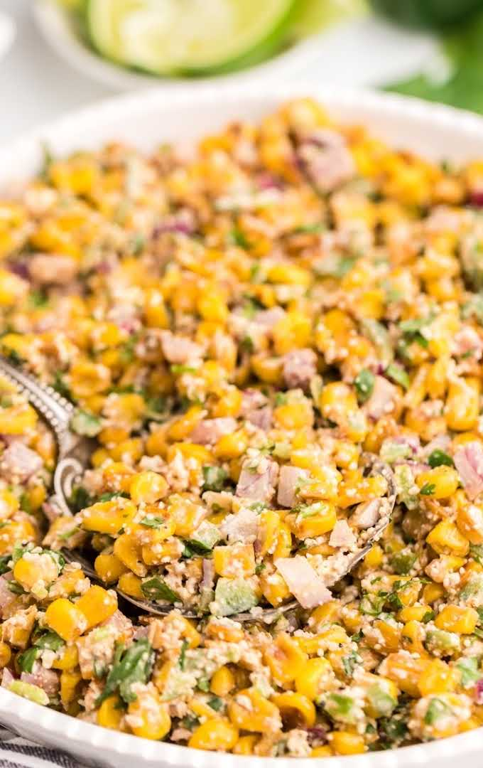 close up overhead shot of Mexican corn salad being picked up with a spoon in a bowl