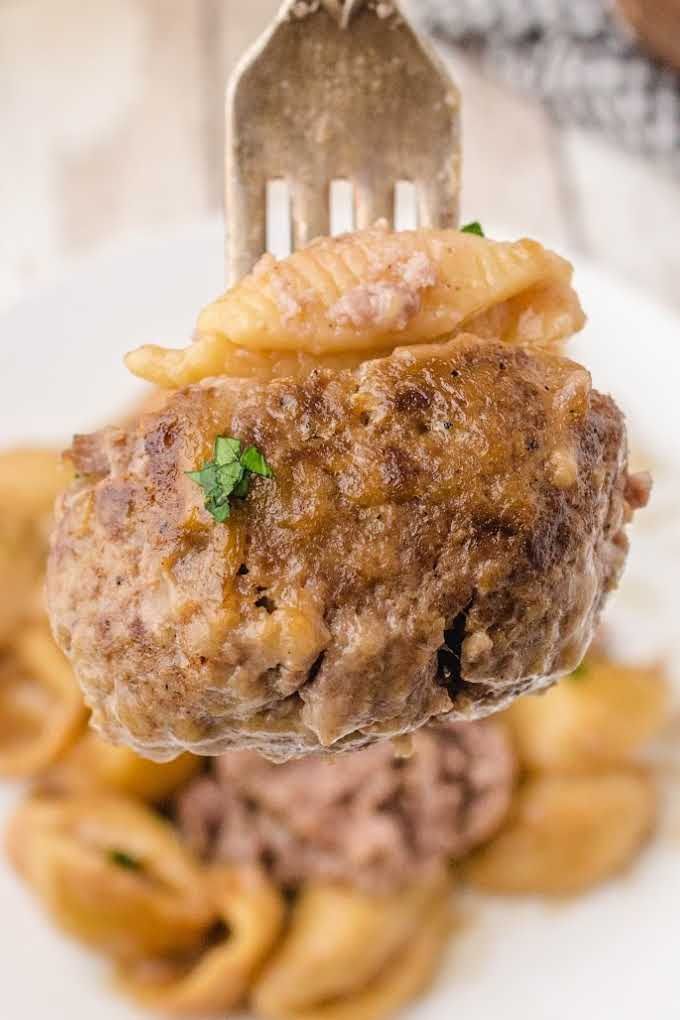 close up shot of swedish meatballs and noodles on a fork