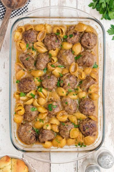 overhead shot of swedish meatballs and noodles garnished with parsley in a pan