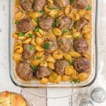 close up overhead shot of swedish meatballs and noodles garnished with parsley in a pan
