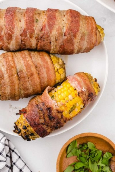 overhead shot of bacon-wrapped corn on the cob on a white plate