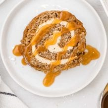 overhead shot of a slice of caramel banana cake roll drizzled with caramel sauce on a plate
