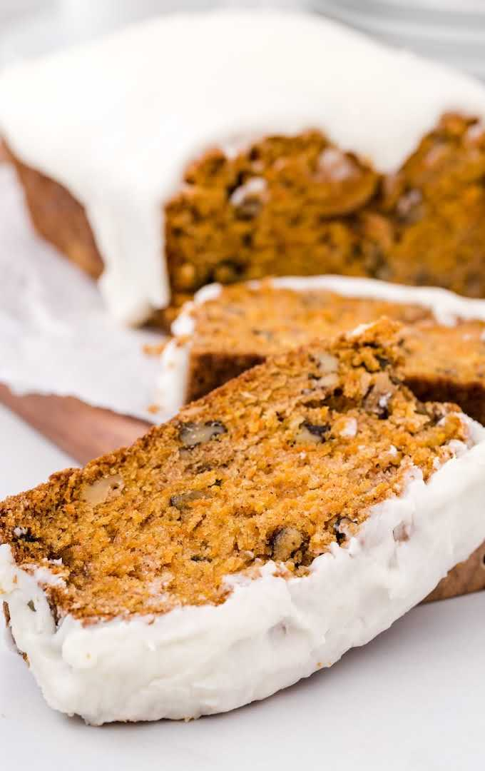 close up shot of a loaf of carrot bread sliced on a wooden tray