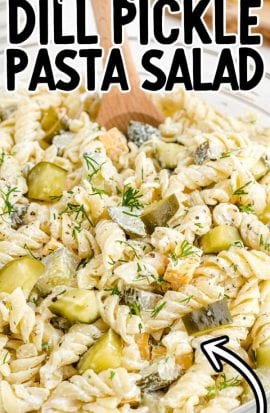 close up overhead shot of dill pickle pasta salad in a clear bowl with a large wooden spoon