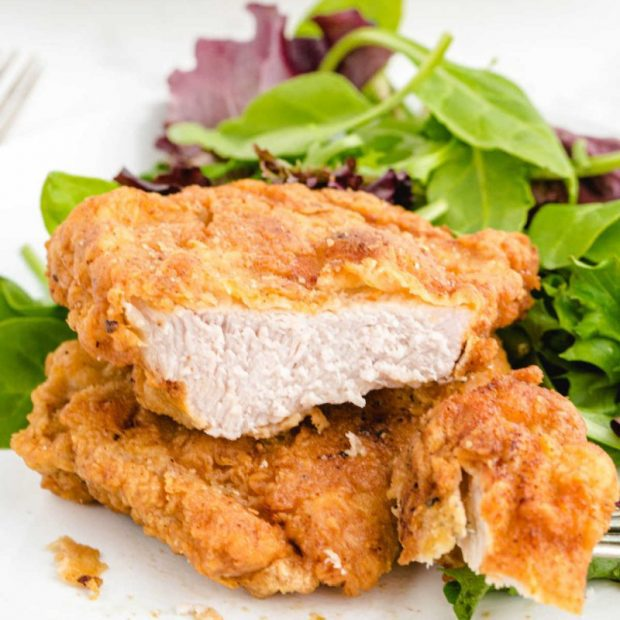 Fried Pork Chops on a plate with a side of salad