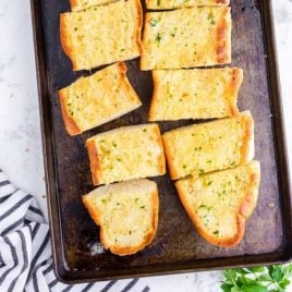 overhead shot of slices of garlic bread on a tin pan