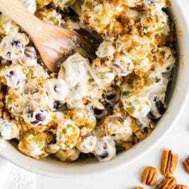 close up overhead shot of grape salad garnished with diced pecans and brown sugar in a bowl with a wooden spoon