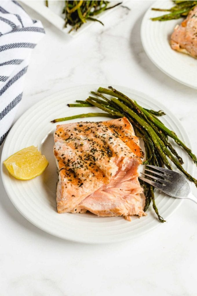 grilled salmon on a plate with asparagus and a slice of lemon